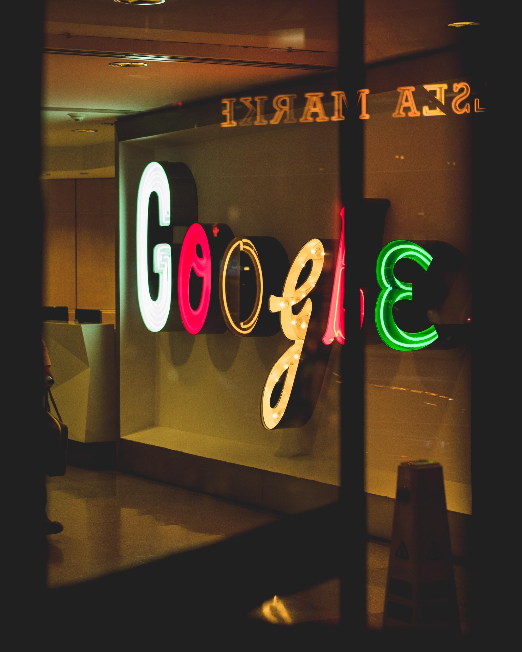 Oficina oscura y letras en neon donde se lee Google
